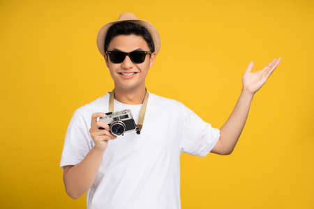 Happy young asian male tourists with open hand gestures and camera isolated on yellow background.