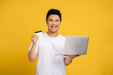 Young Asian man in casual clothes smiling with a laptop and a credit card. Isolated on yellow background. Banco de Imagens