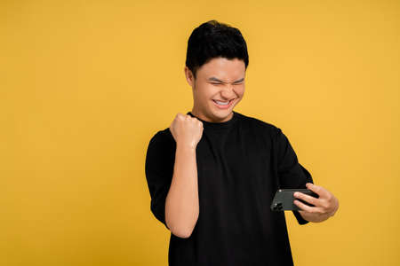 Happy smiling face of a young Asian man using a smartphone. Banco de Imagens