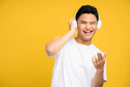 Young Asian man in casual clothes enjoys listening to music. He wears wireless headphones.