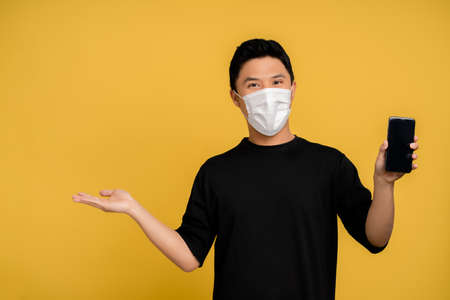 Young Asian man in casual clothes and protective masks wearing a mask He showed his smartphone with his other hand open on a yellow background.