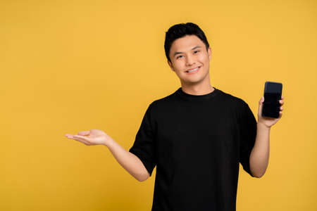 Young Asian man in casual clothes is smiling happily. He showed his smartphone with his other hand open on a yellow background.