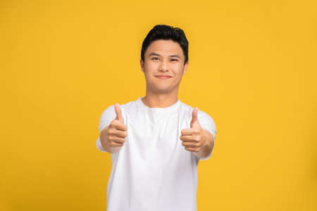 Portrait of a handsome Asian man smiling and thumbs up against a yellow background. Banco de Imagens