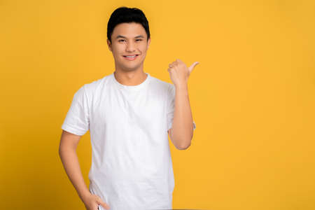 Young Asian man wearing a white T-shirt is pointing his finger with a happy face with copy space on a yellow background.