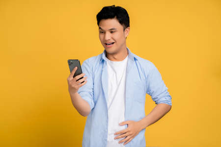 Young Asian man in casual wear uses a smartphone. He was shocked. Isolated background.
