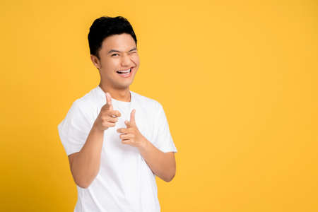 Young Asian man wearing a white T-shirt is pointing a finger with a happy face. Isolated background.