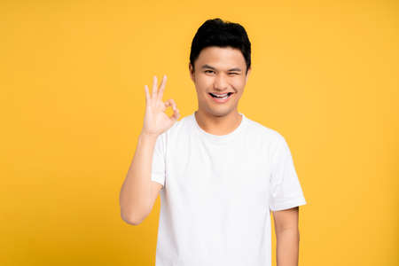 Young Asian men showing okay gestures isolated on a yellow background. Banco de Imagens