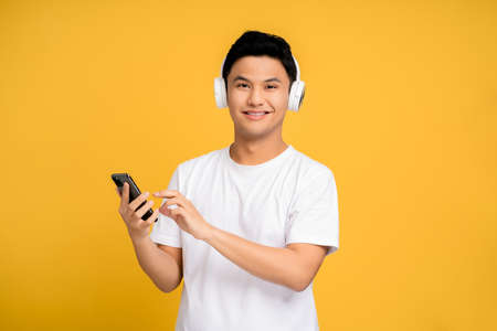 Young Asian man wearing a white T-shirt is using a smartphone and wireless headphones.