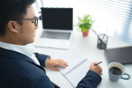 Young Asian businessmen are using a laptop and taking notes on the white desk in the office