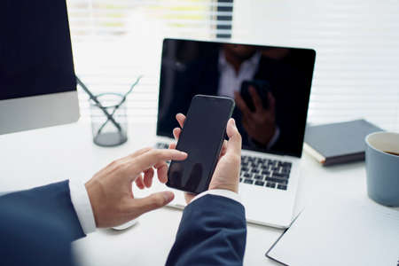 Close-up of a young Asian businessman's hand holding mobile phone and touching screen on desk in an office. Social networks and business concept.