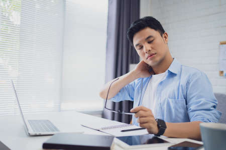 Feeling tired. Young Asians stressed and very tired after working long hours on the desk. Banco de Imagens