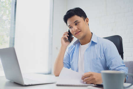 Young Asian businessman talks on the phone and watches his laptop during the workflow at work.