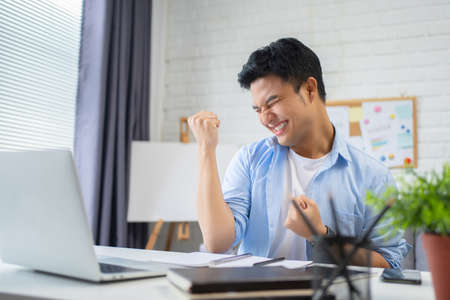 Young Asian men celebrate success in the workplace.