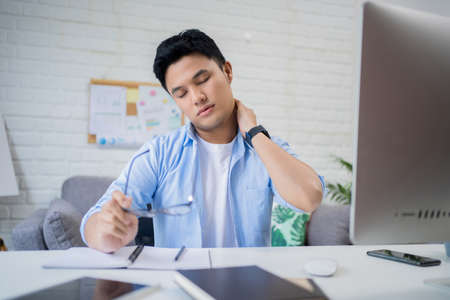 Young Asian man is tired after sitting at work and holding glasses in his hand.
