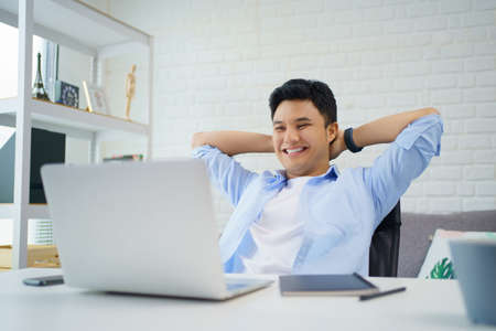 Young Asian man is smiling and reading the screen on laptop while relaxing and working at home. Banco de Imagens