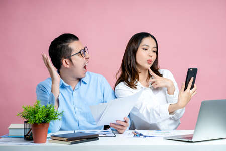 Beautiful woman takes a selfie with a smartphone and a young man feels dissatisfied and scolds. He holds documents in hand. Concept work together. Isolated on a pink background.