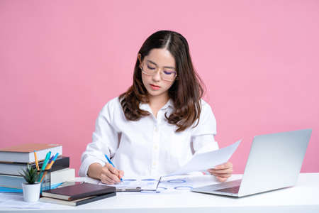 Asian woman wearing glasses and a white shirt sits at a white desk with a laptop in the office. Isolated on a pastel pink background.
