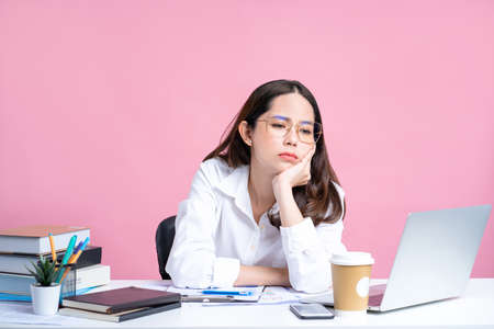 Young Asian women are tired from office work. Isolated Pastel Pink Background.