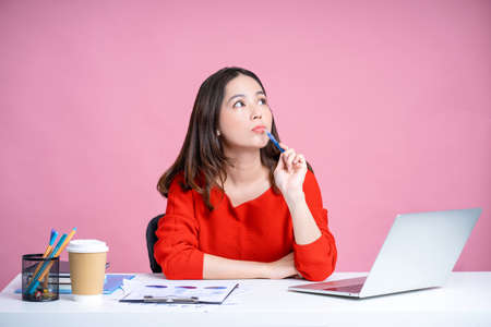 Young Asian woman was thinking about something with holds a pen near her chin and looks up at her desk. Isolated pastel pink background.