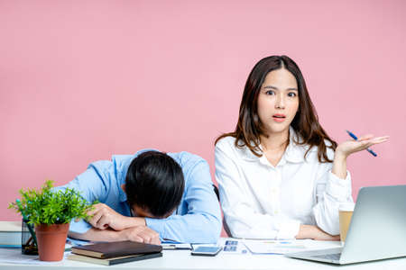 Beautiful woman was dissatisfied with the actions of her colleague. He was so tired he slept on his desk on a pastel pink background.