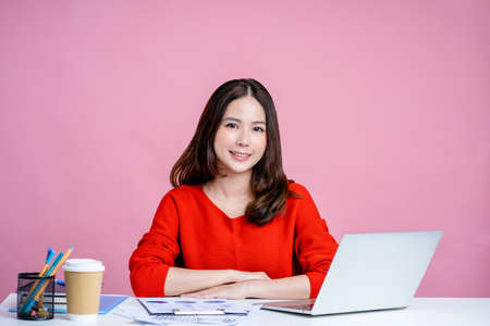 Portrait of a smiling Asian woman sitting at her desk on a pink background.