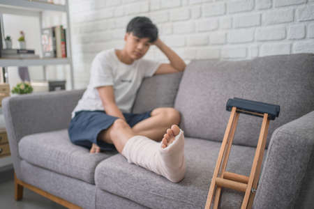 Asian people with broken leg recovering at home.