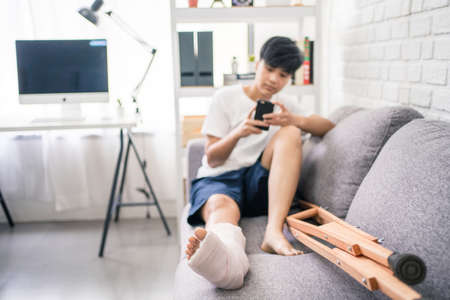 Asian people broken leg with crutches. She recuperates on the sofa at home.