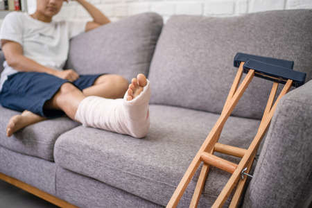 Young Asian man with a broken leg sitting on the sofa. Close up of the crutch.