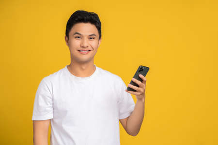 Asian handsome young man smiling and happy. He holds a smart phone on a yellow background.