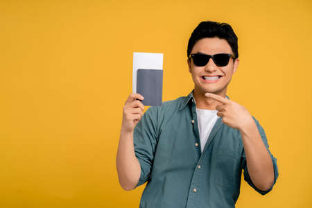 Asian man in casual clothes holds a passport in hand. He's so happy on the yellow background in the studio.