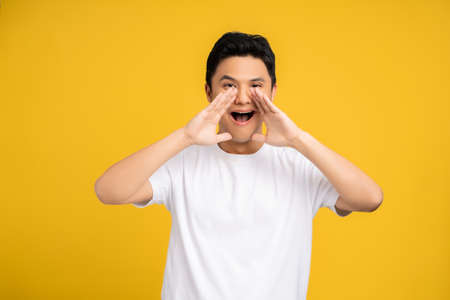 Young Asian man is shouting something on a yellow background in the studio