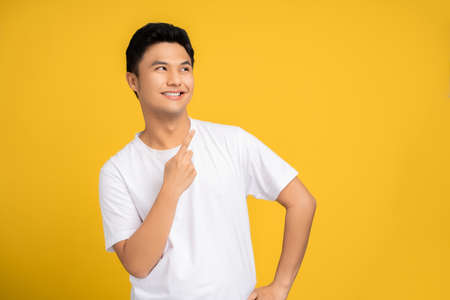 Young Asian man smiles and points his finger to the top isolated on a yellow background.