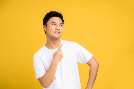 Handsome healthy Asian young man smiling with pointing fingers isolated on a yellow background.