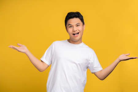 Portrait of an Asian man wearing a white T-shirt was excited for something. He showed an open hand gesture on the yellow studio background. Stock fotó