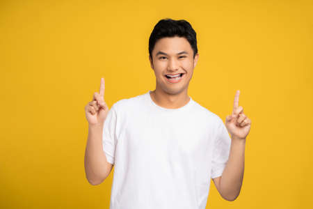 Handsome Asian young man is smiling and happy on a yellow background. He was raising his hand pointing up to the empty space above.