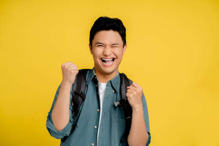 Young Asian male tourists are very happy and excited with hands raising their fists successfully in yellow background studio. Stock fotó