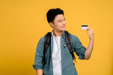 Young Asian man in casual wear holding credit card on yellow background