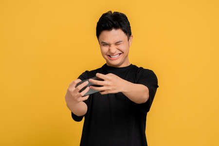 Young Asian people enjoy playing games with your phone. Yellow background isolated