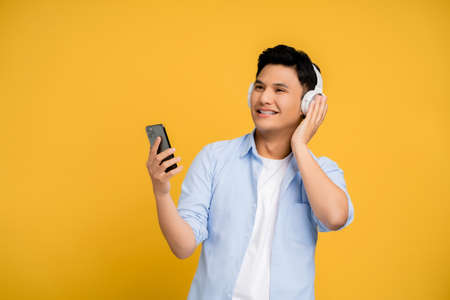 Handsome young Asians using a smartphone and wireless headphones. He listens to music on the phone.