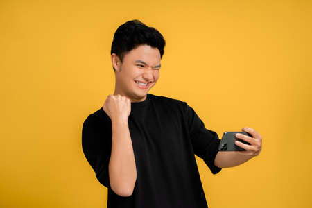 Young Asian man in a cheerful black T-shirt is taking a selfie with a mobile phone showing the winner's gesture. Yellow background isolated.