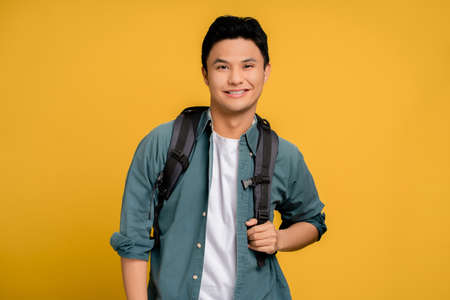 Portrait of young man in backpacking Asian tourists smiling happily in casual clothes on yellow background. Stock fotó
