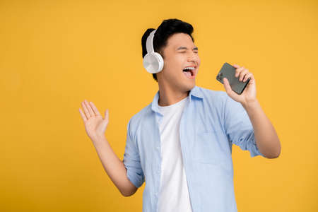 Young Asian man happily sings his favorite song. He is holding a smartphone Stock fotó