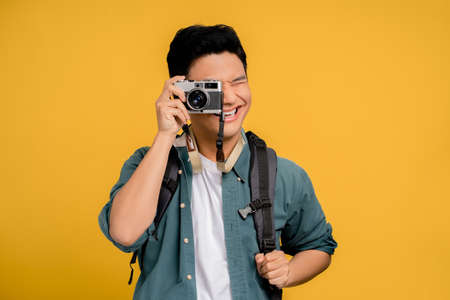 Portrait of a young backpacker Asian tourist taking a picture on a yellow background. He is very happy.