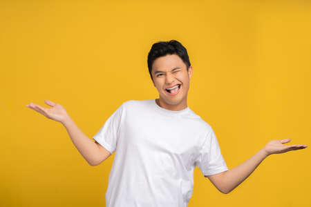 Asian man wearing a white T-shirt was excited for something on a yellow studio background with copy space. Stock fotó