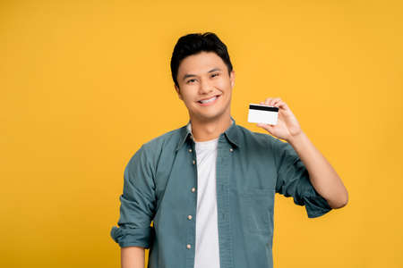 Happy young Asian men in casual clothes. He shows his credit card on a yellow background. Stock fotó