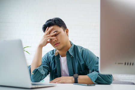 Portrait of a young Asian man wearing casual clothes sits at a white desk with a laptop computer. He is stressed.