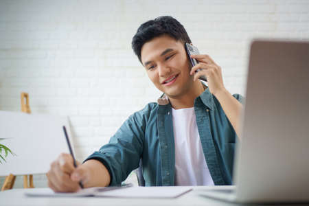 Young Asian man in casual clothes is taking notes while talking on the phone on the desk in the room. Stock fotó