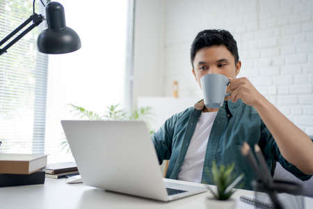 Young Asian man drinking hot coffee and using a laptop on a white desk in the room.