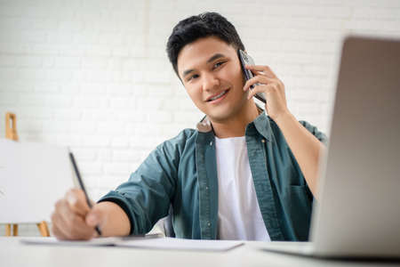 Portrait of a young Asian man in casual clothes sits at a white desk. He is taking notes and talking on the phone.
