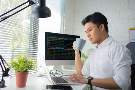 Young Asian man drinking coffee while looking at a monitor with financial information in the office. Online Trading Concepts. Stock fotó